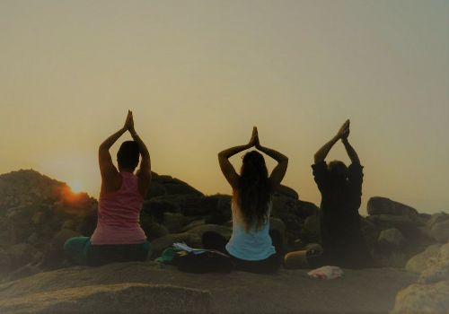 Three People doing relaxing yoga at sunset