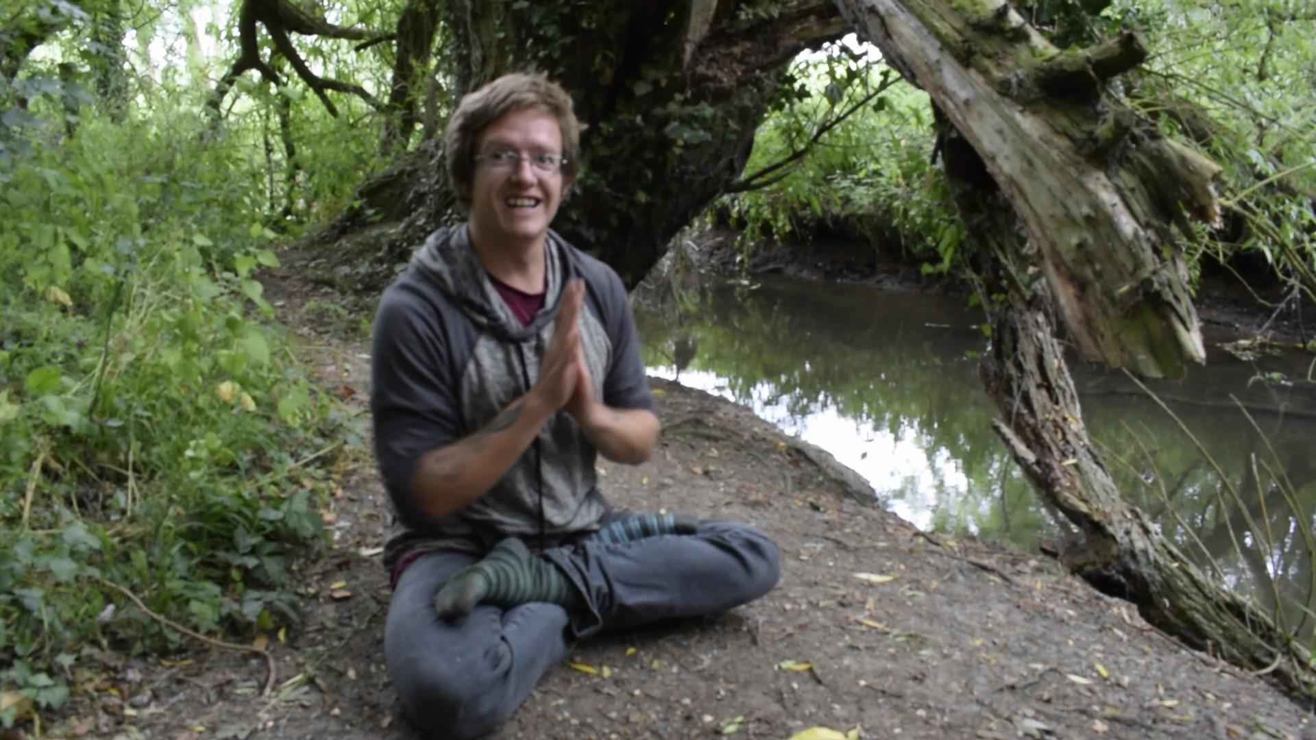 Picture of Laurence smiling by a river, his hands are in a Yoga Prayer position, Sudbury, Suffolk. Norwich